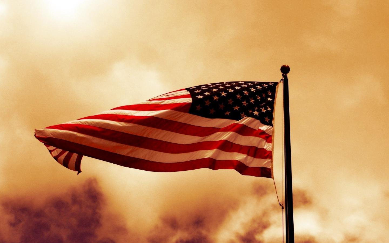 Флаг США на фоне дыма и заката